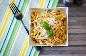 Draufsicht von Bandnudeln mit Pesto und geriebenem Käse