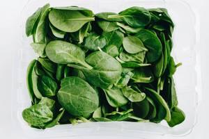 Draufsicht von frischem Spinat vor weißem Hintergrund