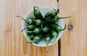 Draufsicht von grünen Paprika auf einem Holztisch