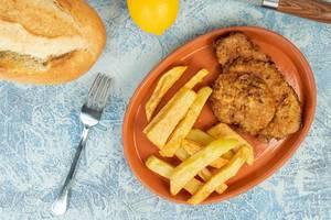 Draufsicht von Hähnchen Schnitzel mit Pommes auf einem Teller mit Brötchen und Zitrone