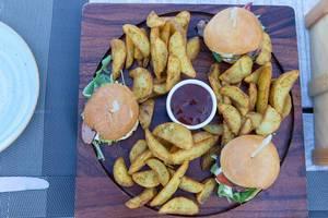 Draufsicht von Hamburgern und Bratkartoffeln im Aelia Restaurant Kassandra