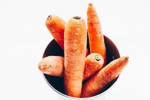 Draufsicht von Karotten in einer Schüssel. Weißer Hintergrund. Nahaufnahme