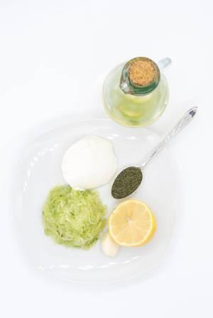 Draufsicht von Zutaten für griechischen Tsatsiki: geriebene Gurke, Zitronensaft, Öl, Sauerrahm und Dill