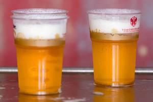 Drei Bier in Plastikgläser mit dem Slogan des Tomorrowland Festivals im roten Hintergrund