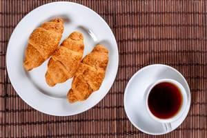 Drei Croissants auf einem Teller und eine Tasse Tee in der Aufsicht