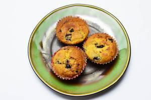 Drei frisch gebackene Blaubeer-Muffins auf grünem Teller