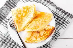 Drei gebratene Pfannkuchen neben einer Gabel, auf einem Teller und Geschirrtuch