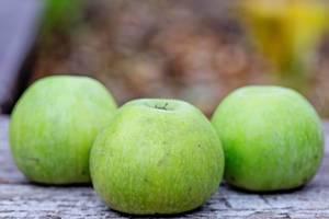 Drei grüne Äpfel auf einem Holztisch