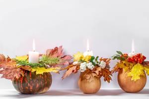 Drei Herbstlich geschmückte Kürbisse mit Kerzen und bunten Blättern auf weißem Hintergrund