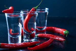 Drei kleine Gläser gefüllt mit Wodka mit scharfen roten Chilis vor schwarzem Hintergrund