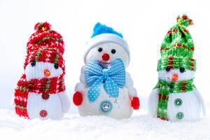 Drei kleine Schneemänner mit Mütze und Schal im Schnee