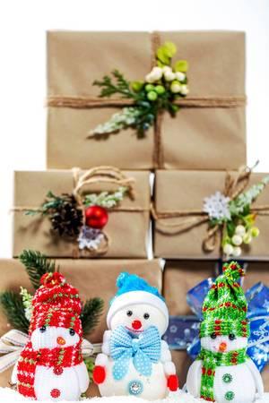 Drei kleine Schneemänner vor einem Stapel Weihnachtsgeschenke im Schnee