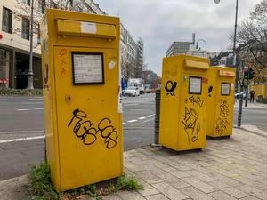 Drei mit Graffiti bemalte, gelbe Briefkästen der Deutschen Post an Straßenkreuzung