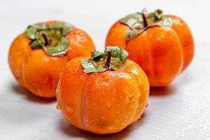 Drei, reife, orangene Persimonen auf weißem Holzhintergrund