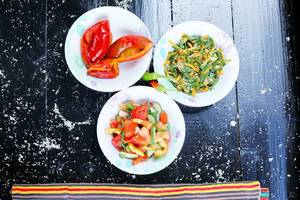 Drei Salatschüsseln auf einem schwarzen Hintergrund, Aufnahme von oben: eingelegte Paprika, frisches Gemüse-Mix und Karottensalat
