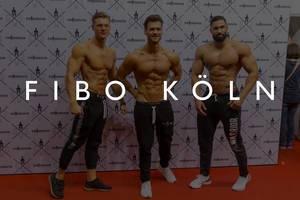 """Drei sportliche Männer mit nacktem Oberkörper zeigen ihre Muskeln und Sixpacks auf dem roten Teppich, mit dem Bildtitel """"Fibo Köln"""""""