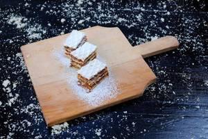 Drei Stück hausgemachter Karamellkuchen auf einem Holzbrett vor einem schwarzen Hintergrund