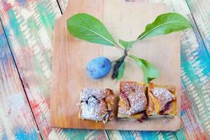 Drei Stück Pflaumenkuchen mit einer frischen Pflaume auf einem Holzbrett