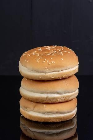 Drei ungefüllte, gestapelte Hamburgerbrötchen isoliert vor schwarzem Hintergrund