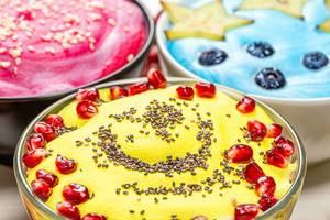 Drei verschiedene Varianten von Haferflocken-Schüsseln, mit bunter Creme, Granatapfel, Samen und Blaubeeren
