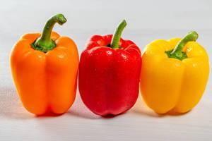 Drei verschiedenfarbige Paprika mit Stengel, auf einem weißen Küchentisch