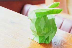 Dreidimensionaler ausgedruckter grüner Hase aus dem 3D-Drucker, steht im Sonnenlicht auf einem Holztisch