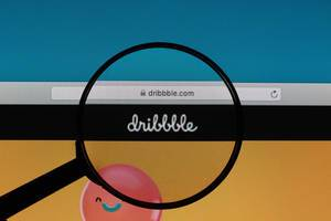 Dribbble logo under magnifying glass