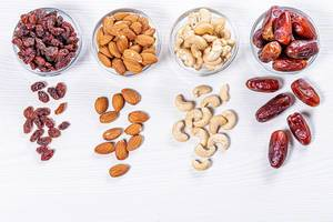 Dried dates, raisins, cashew nuts and almonds on white wooden background (Flip 2019)