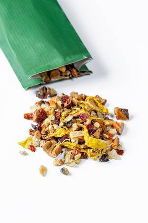 Dried fruit and flower tea spilled from the package on a white background