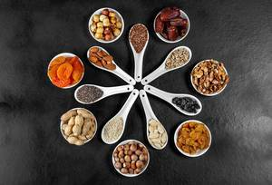 Dried fruits, nuts and seeds in spoons and bowls on a black background. Top view (Flip 2020)