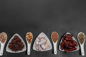 Dried fruits, nuts and seeds on a black background with free space. Healthy food concept