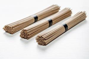 Dried raw Japanese soba noodle stick on white wooden background