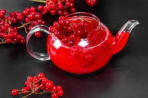 Drink in a glass teapot with fresh viburnum berries on a black background (Flip 2019)