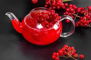Drink in a glass teapot with fresh viburnum berries on a black background