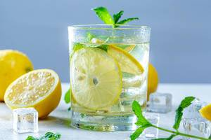 Drink with fresh lemons, mint and ice in glass