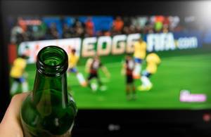 Drinking beer and wathing football on TV