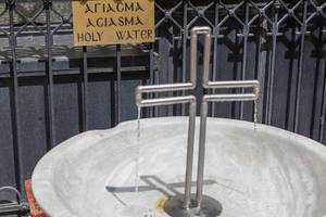 Drinking fountain with holy water in the shape of a cross