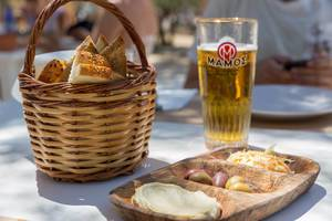 Drinks and a bread basket, next to Mediterranean food, like humus and olives, in a Greek restaurant on Paros Island