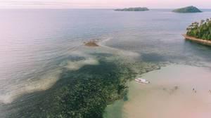Drohnen-Aufnahme der Sulusee mit einer Insel und einem Boot vor Punta Bulata