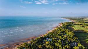 Drohnenaufnahme der Küste von Hinigaran mit braunem Sandstrand und grünem Hinterland, Insel Negros, Philippinen