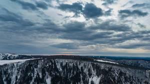 Drohnenaufnahme verschneiter Bergspitzen bei Sonnenuntergang. Dramatischer Himmel