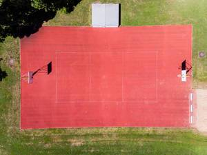 Drohnenaufnahme von rotem Basketballfeld ohne Sportler nahe dem Bayrischen Landtag in München