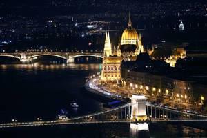 Drohnenbild und Nachtansicht von Budapest und dem beleuchteten Donauufer mit Brücke