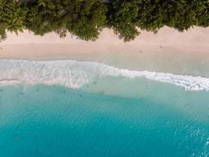 Drohnenbild vom türkisblauen Ozean und Strand Anse Lazio auf der Tropeninsel Praslin, Seychellen