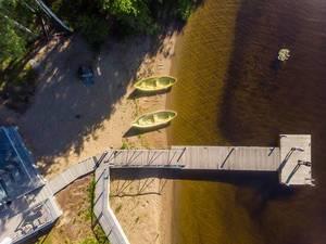 Drohnenbild von einem Holzsteg vor dem Gästehaus Villa Jolla, mit grünen Ruderbooten am Seeufer Päijänne, zwischen Lahti und Jyväskylä