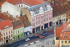 Drohnenbild von Straße und bunten, historischen Häusern in Brasov, Rumänien