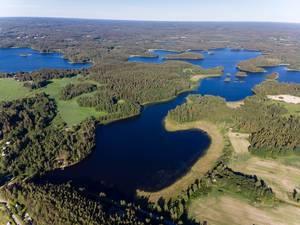 Drohnenbild zeigt Seenplatte in Finnland, mit grünen Waldflächen und unberührter Natur um Padasjoki