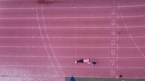 Drohnenfoto einer erschöpften Läuferin, die auf der Laufbahn liegt