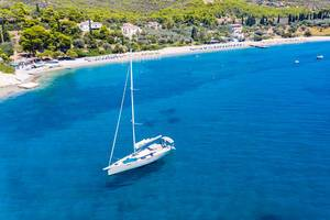 Drone picture of a sailboat on the clear blue Myrtonic Sea, with Spetses Island in the background
