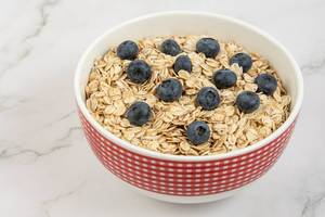 Dry and fresh Oatmeal with Blueberries in the bowl